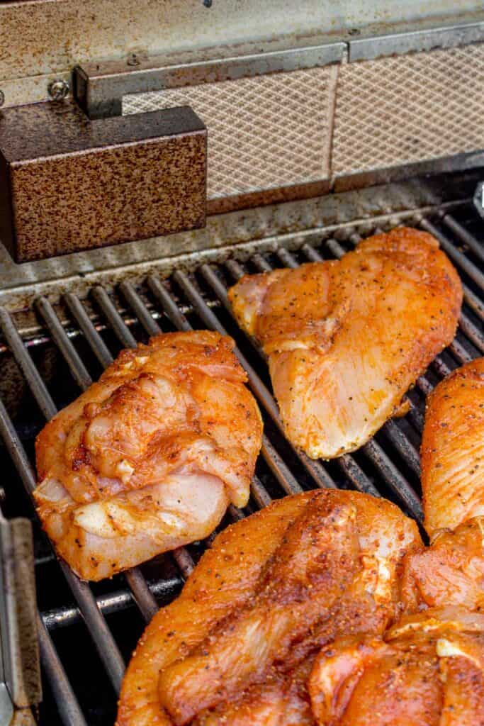 Seasoned chicken breasts on the grill.