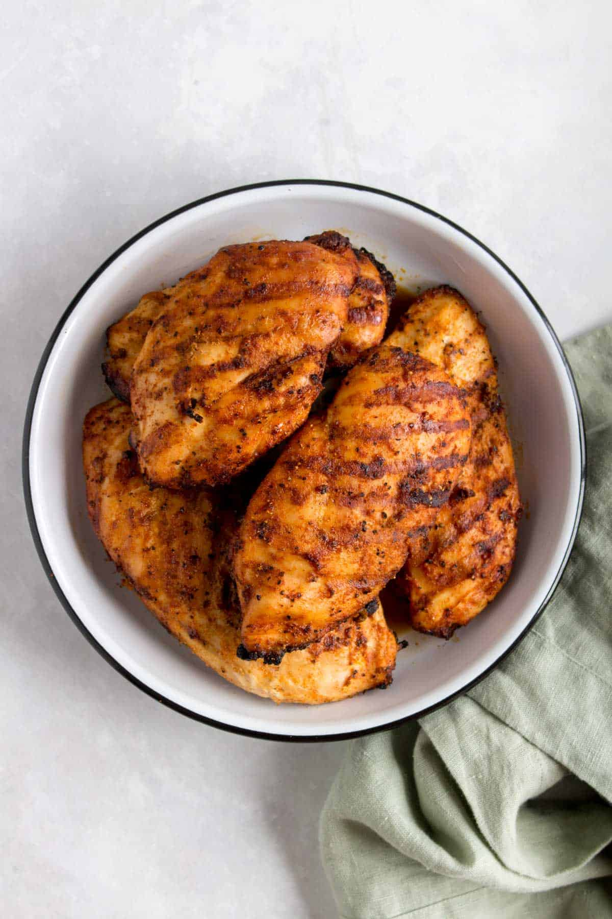 A plate with multiple grilled chicken breasts.
