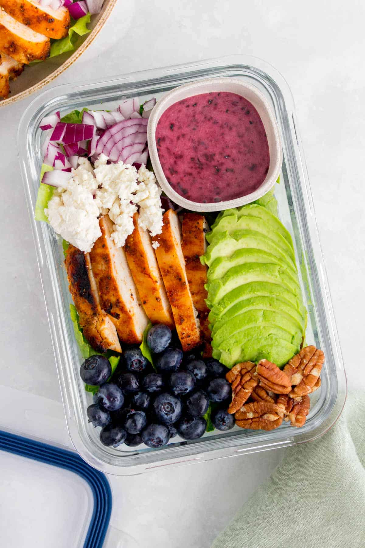 Meal prep container with grilled chicken salad with blueberries, pecans, onions, avocado, and goat cheese with a blueberry vinaigrette.