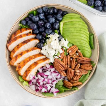 A plate of grilled chicken salad with blueberries, pecans, onions, avocado, and goat cheese.
