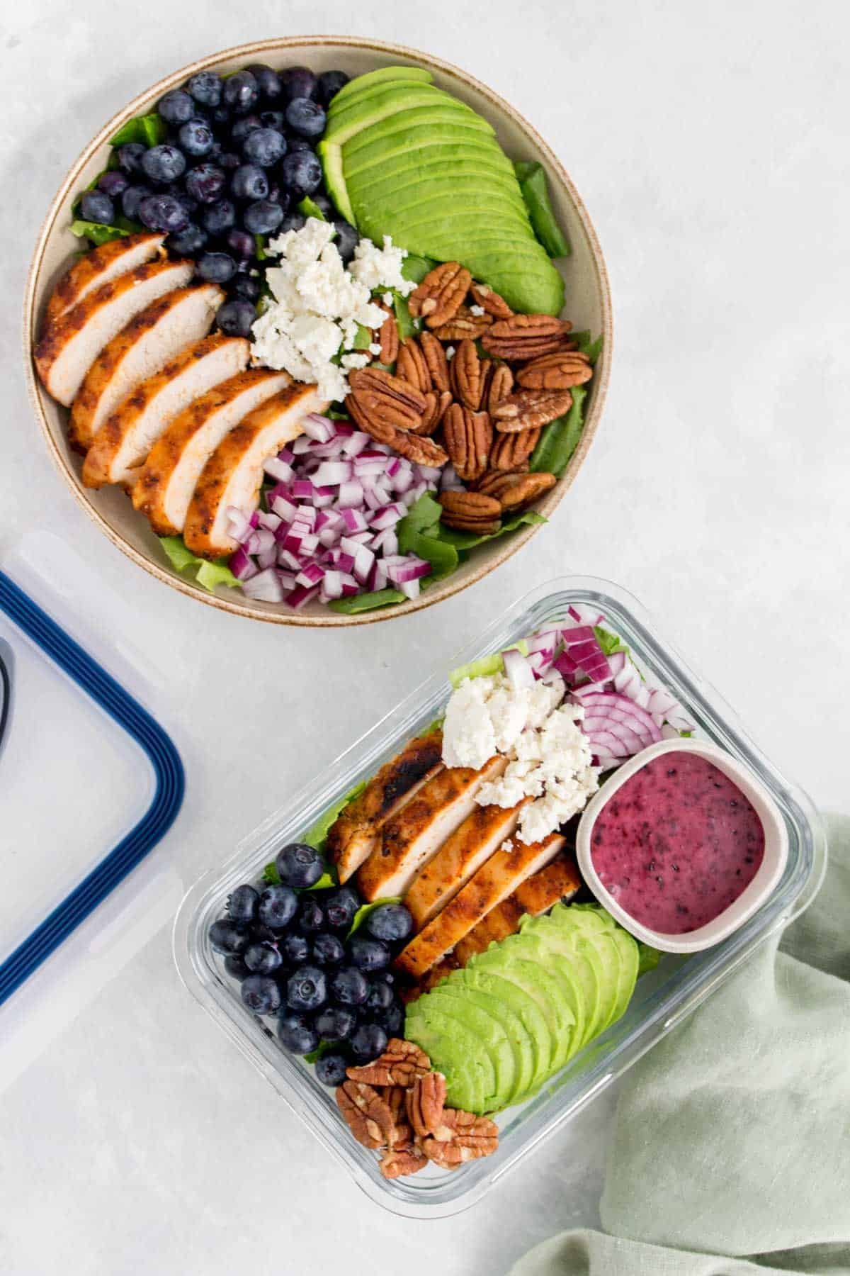 A bowl and a meal prep container with grilled chicken salad with blueberries, pecans, onions, avocado, and goat cheese with a blueberry vinaigrette.