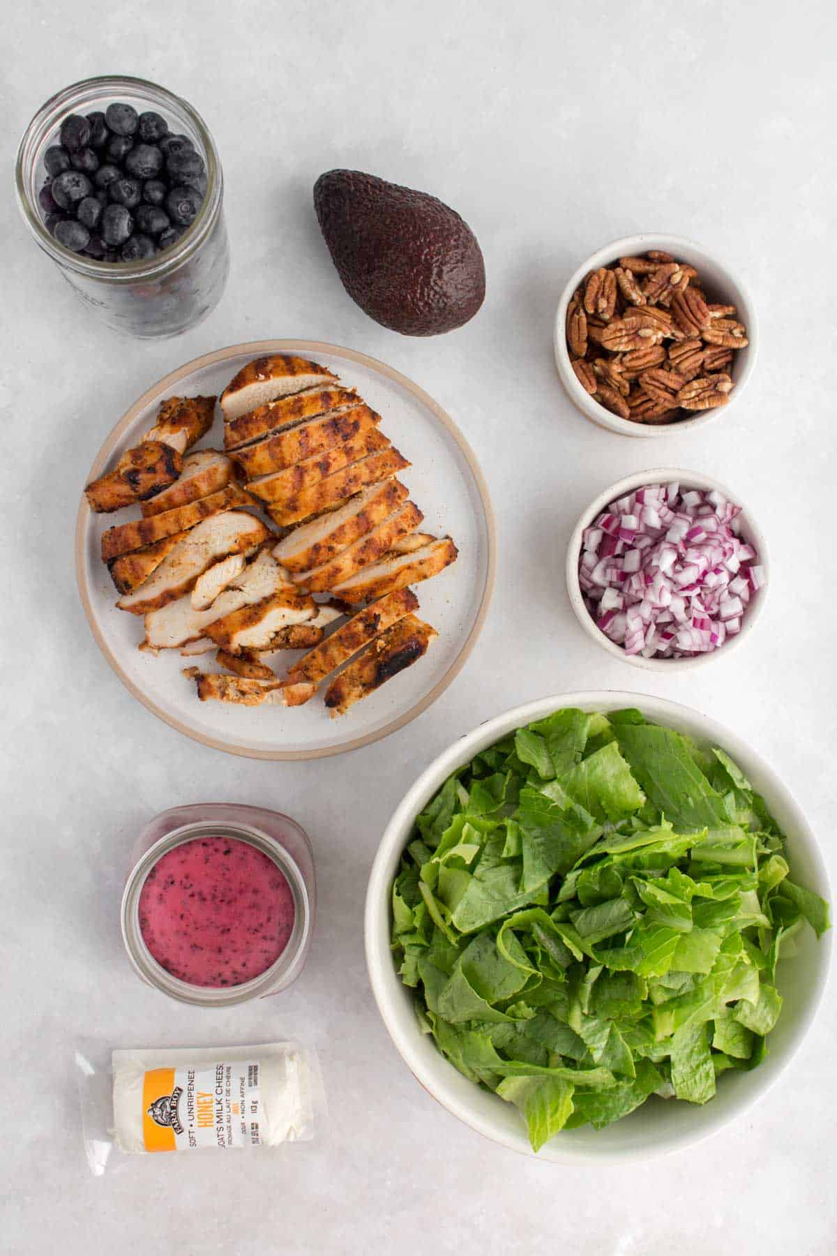 Ingredients needed to make a grilled chicken salad with blueberries.